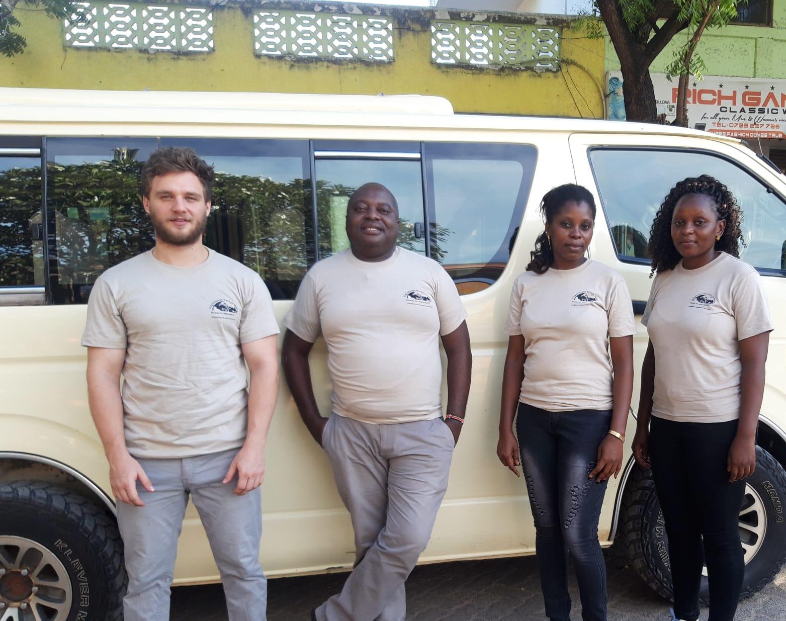 The safari team of KingTomondo Safaris Kenya in front of a safari vehicle